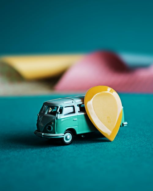 Selective Focus Photo of a Yellow Plectrum Beside a Miniature Van