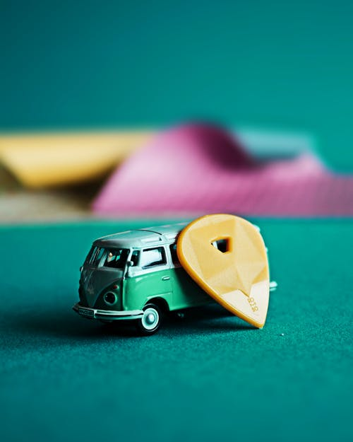 Yellow Guitar Pick Beside a Toy Car