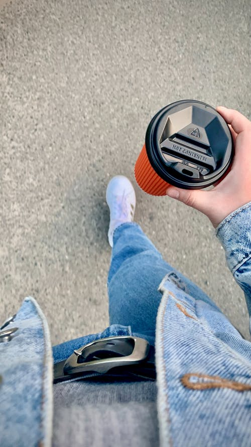 Perspective of a Person in Denim Clothes Holding a Cup of Coffee