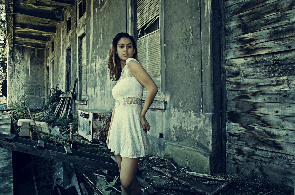 Photo of Woman Wearing White Dress Standing Near Abandoned Building