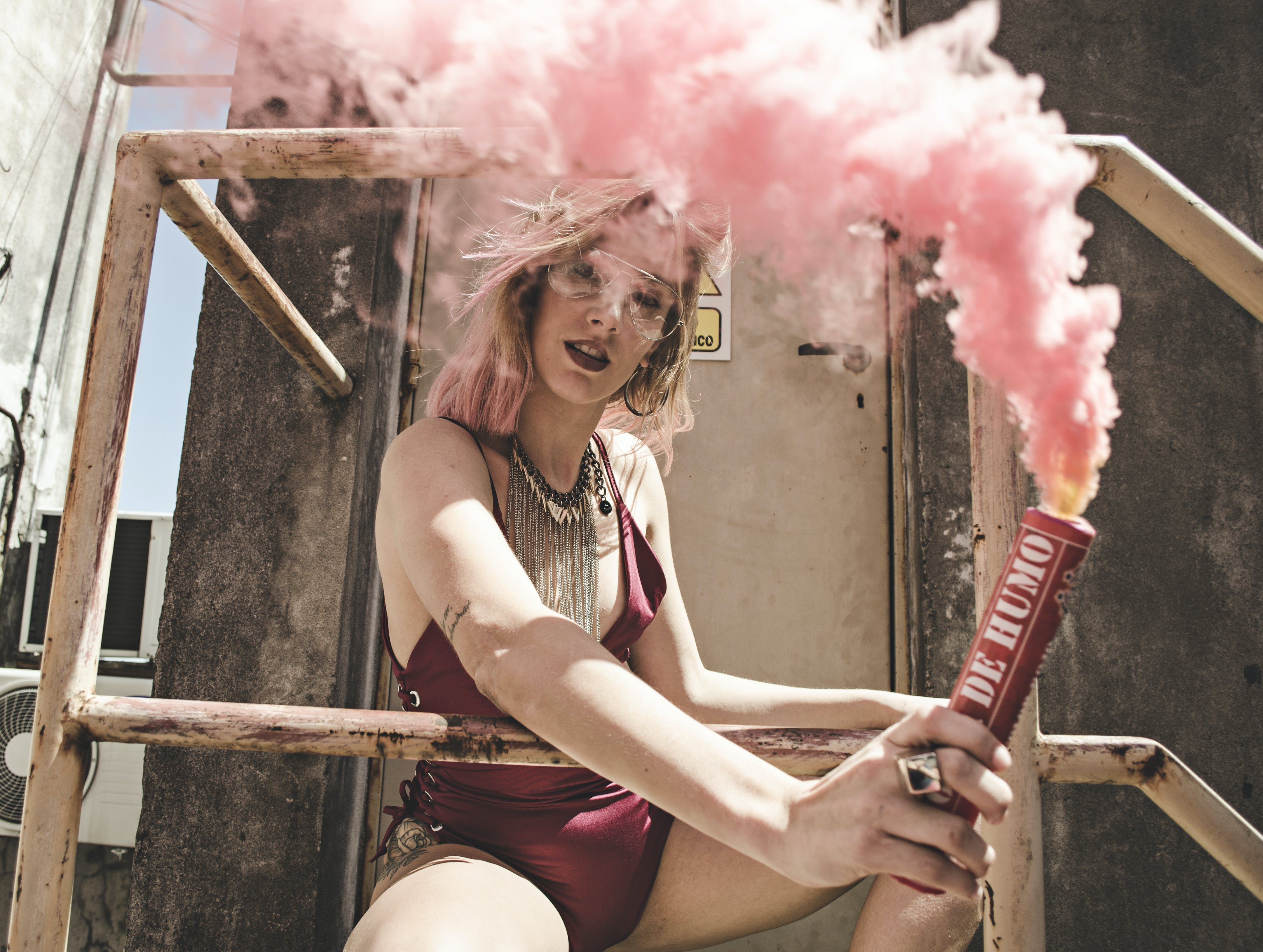 Woman in Maroon Monokini Holding Dynamite