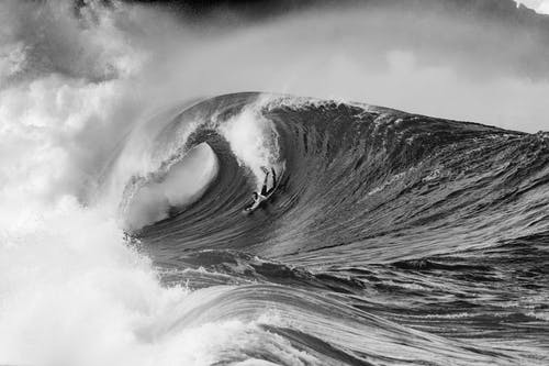 Black and white scenic view of powerful stormy sea with massive foamy waves rolling under cloudy sky