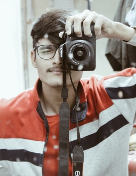 Man in Red and White Full-zip Jacket Holding Canon Dslr Camera