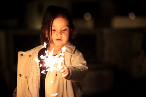 Girl in Beige Button-up Coat Holding Fireworks