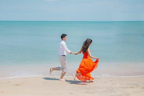 Homem E Mulher Caminham Ao Lado Do Mar Verde