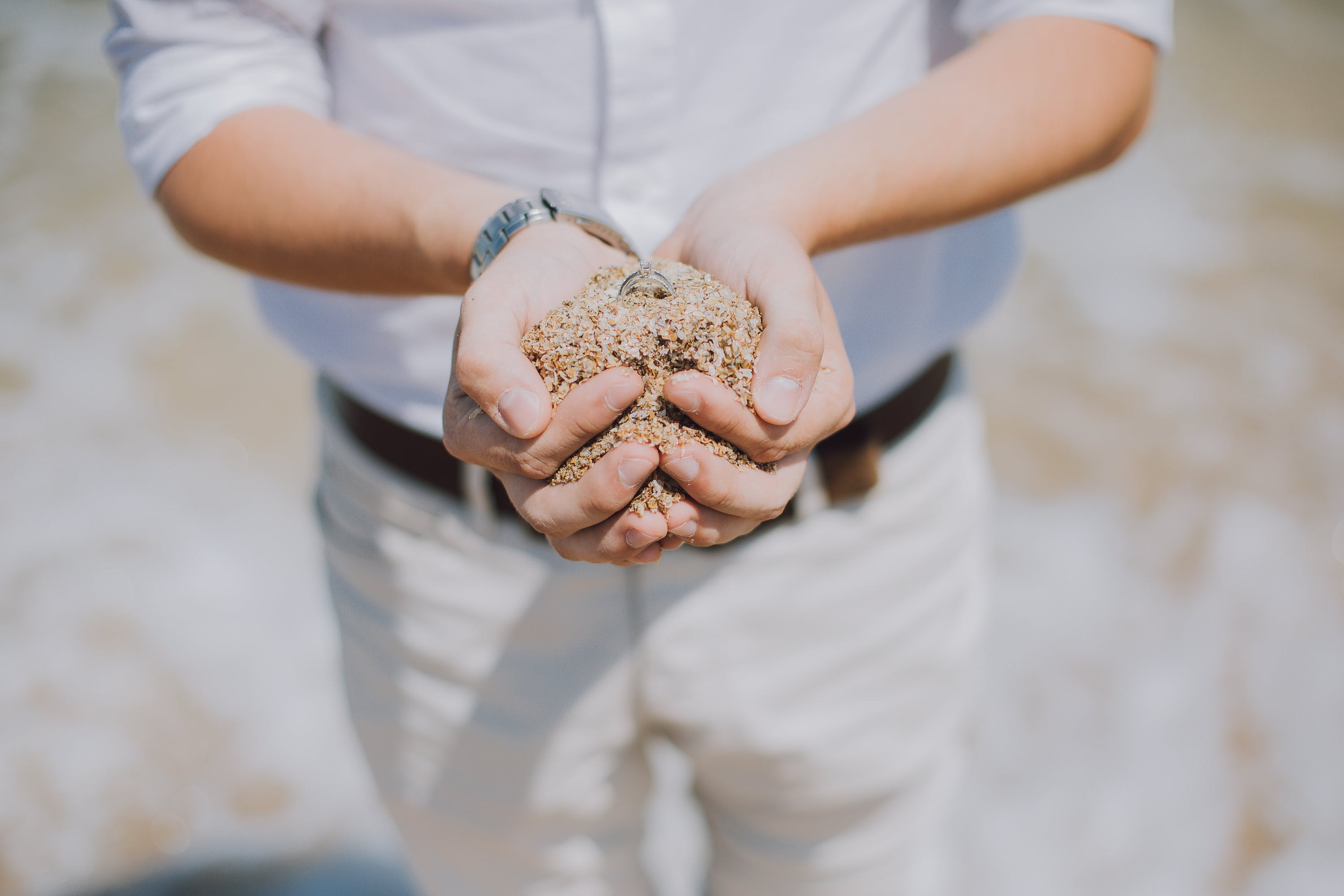 Shallow Focus Photography of Person Holding Brown Sand