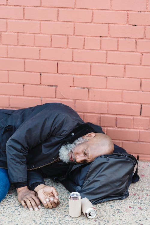 Drunk Man Lying on Ground Next to a Brick Wall