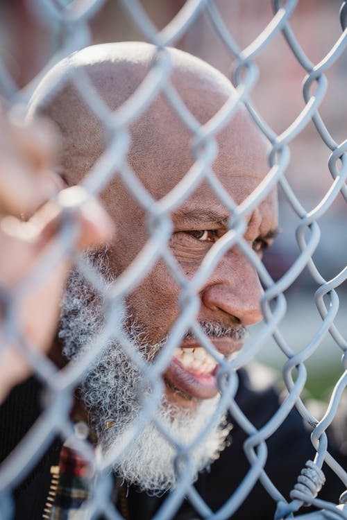 Elderly Bearded Man Behind the Fence