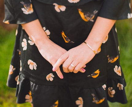Close Up Photo of Person Wearing Black and Orange Floral Dress