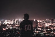 Photography of a Person Watching over City Lights during Night Time