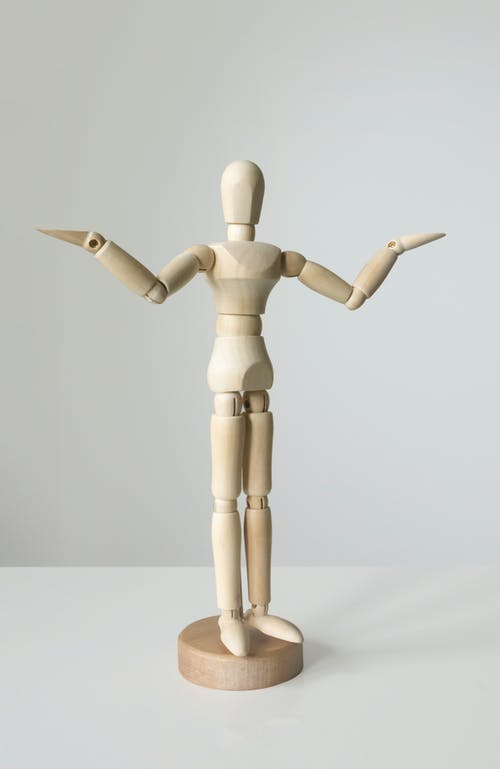 Brown Wooden Human Figure on White Textile