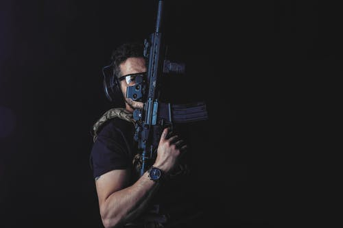 A Man in Black Shirt Holding a Rifle
