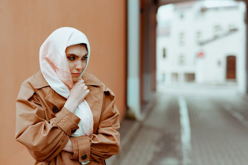 Woman in Brown Coat Wearing White Hijab Standing on the Street