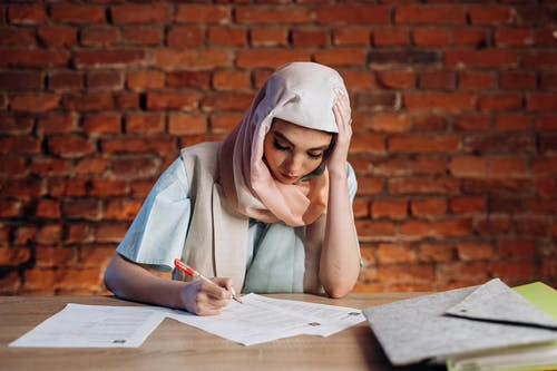 Woman in White Hijab and White Long Sleeve Shirt Writing on White Paper