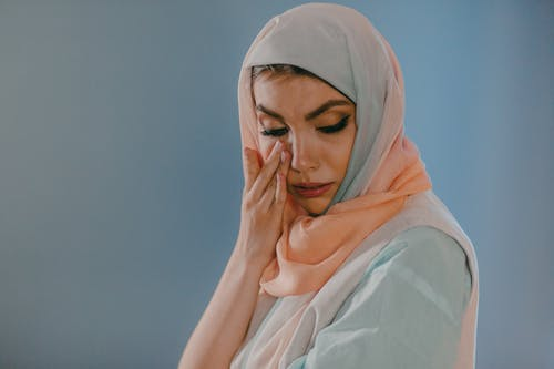 Woman in White Hijab Covering Her Face With Her Hand