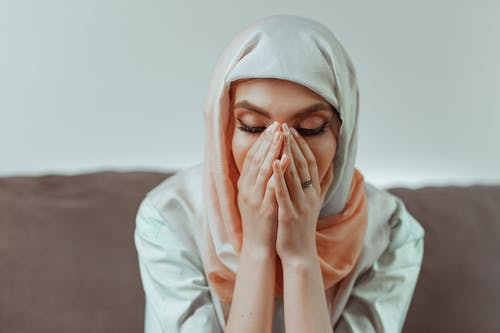 Woman in White Hijab Covering Her Face With White Textile