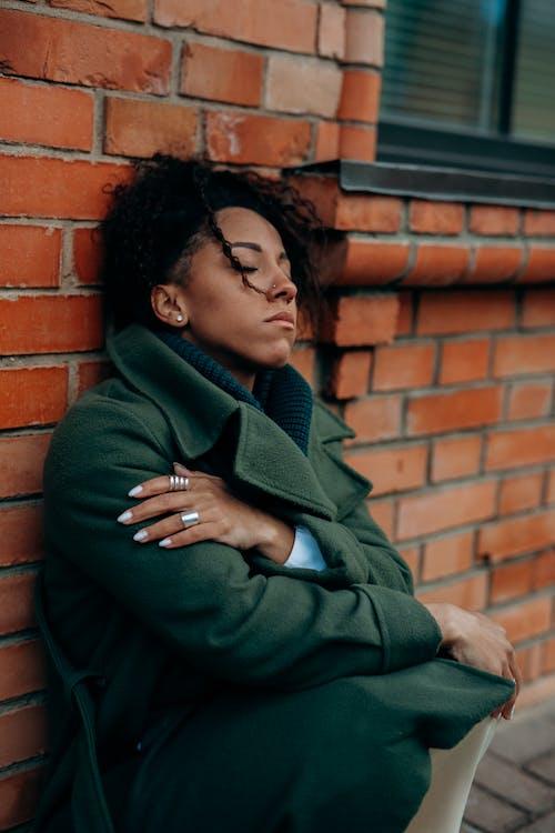 Man in Green Hoodie Sitting on Brown Brick Wall