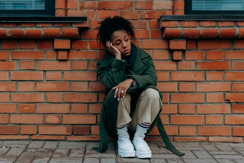 Woman in Green Coat and White Pants Sitting on Brown Brick Wall