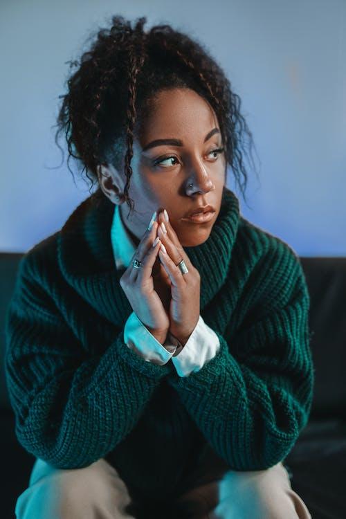 Woman in Green Sweater Sitting on Black Sofa