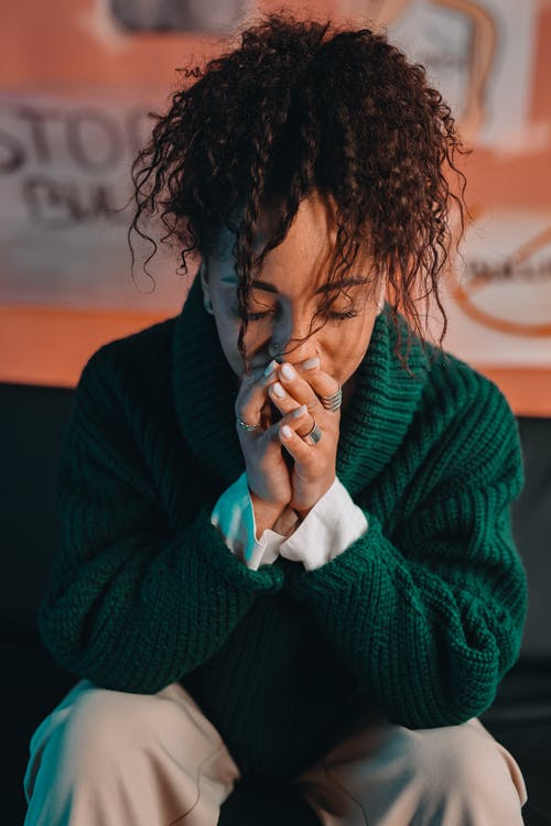 Woman in Green Sweater Covering Her Face With Her Hands