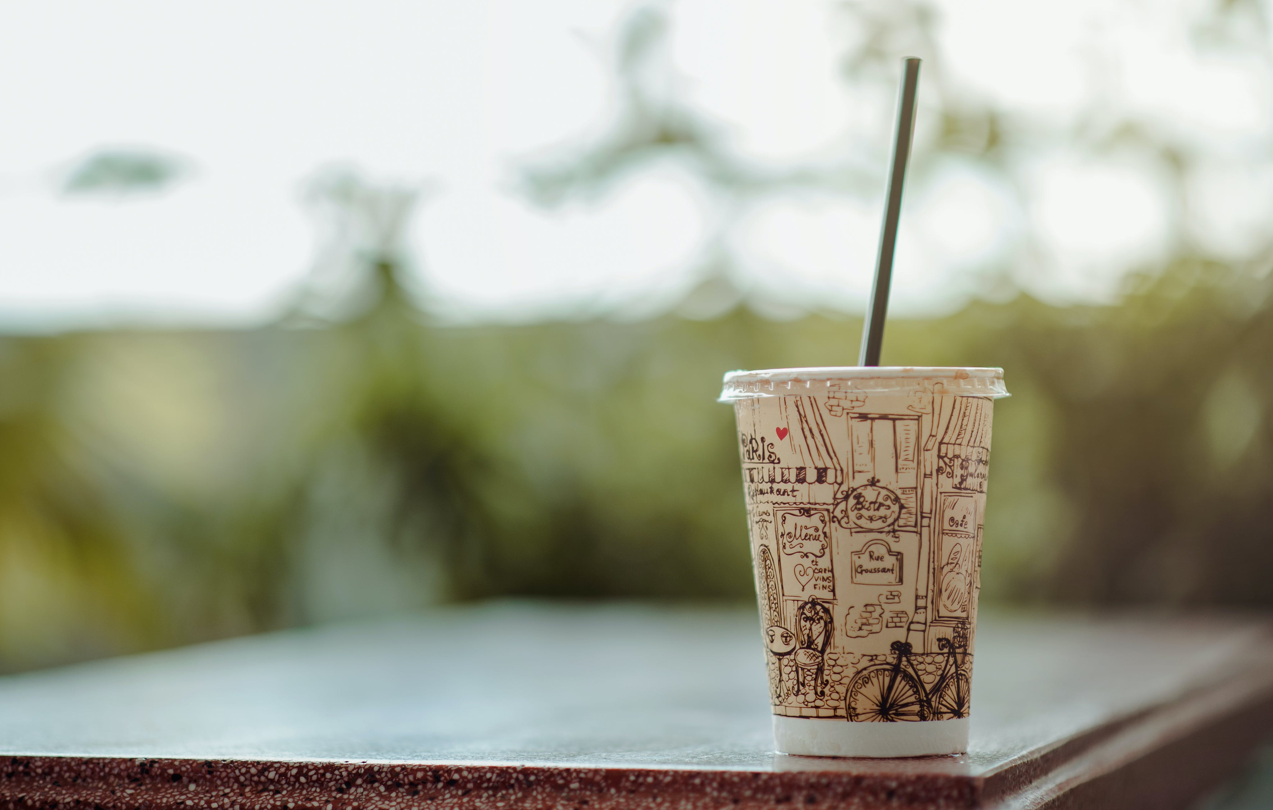 Selective Focus Photo of White Plastic Cup With Lid and Straw