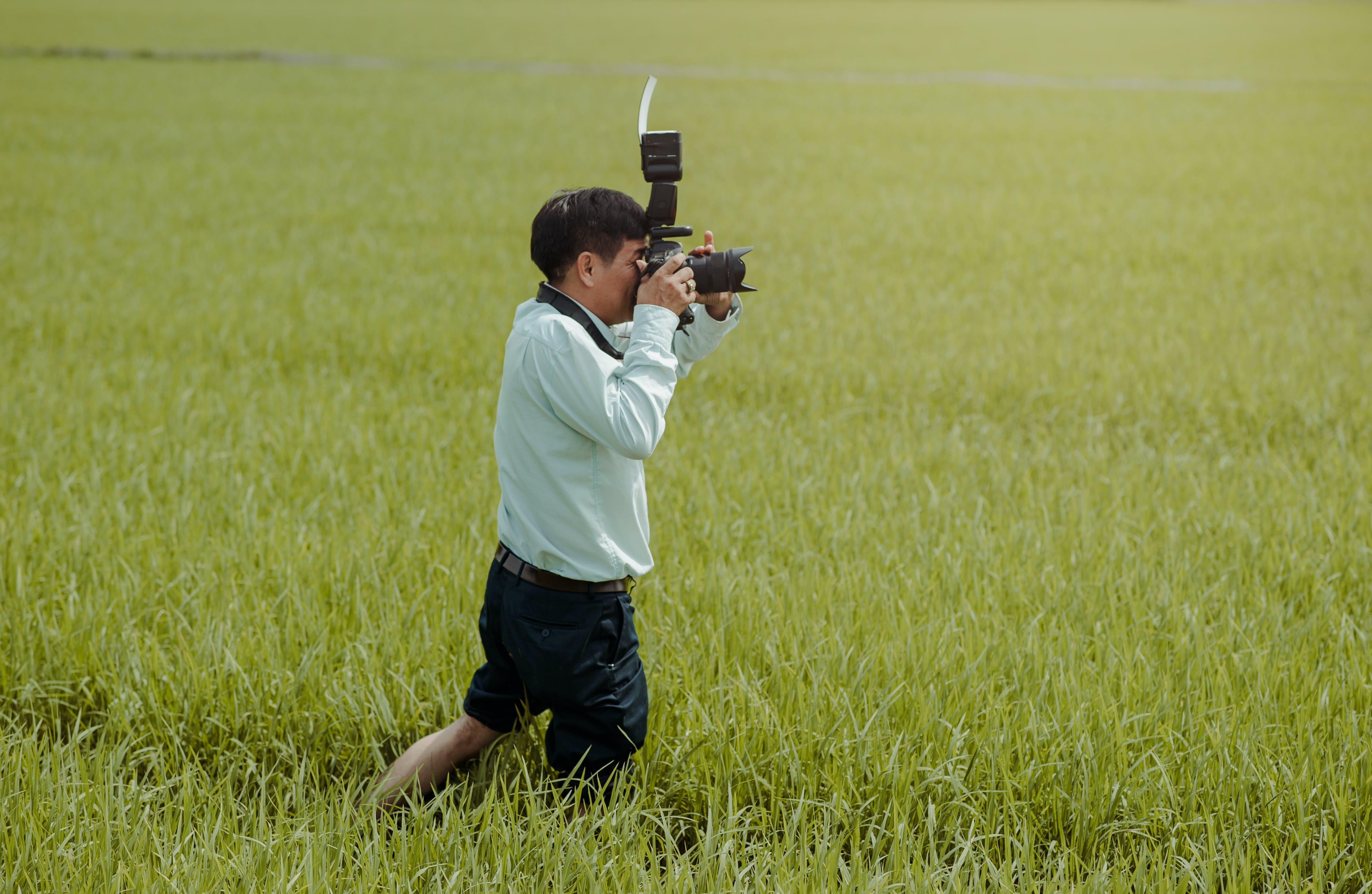 Man Standing on Rice Field Holding Camera