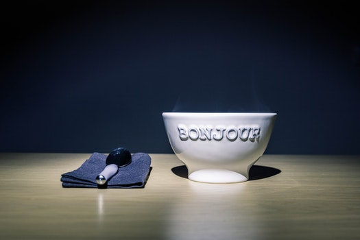 Bonjour Embossed White Ceramic Bowl on Table Beside Stainless Steel Spoon on Black Table Textile