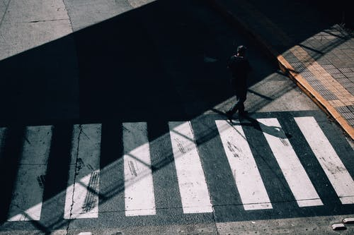 From above full body of anonymous man in shadow strolling on crosswalk of road in sunny day