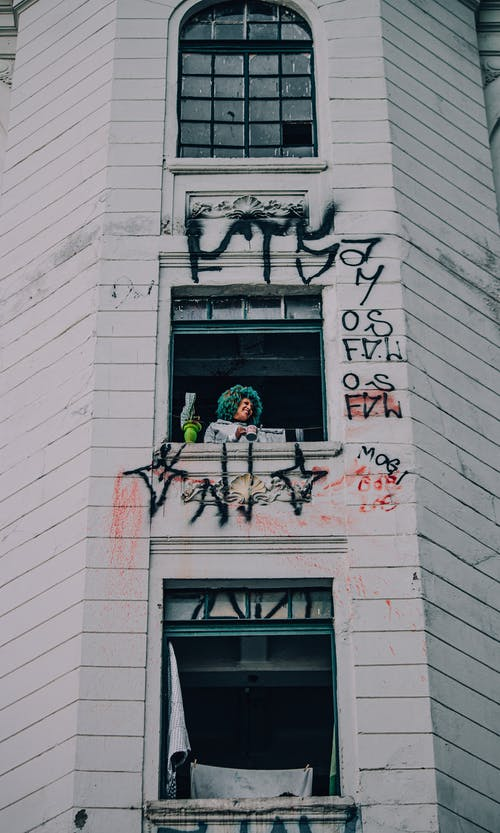 From below of positive female with colorful curly hair standing near window of residential building with vandalized facade