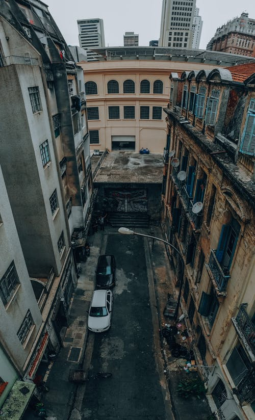 From above of alley with parked cars between aged weathered dwelling in residential district