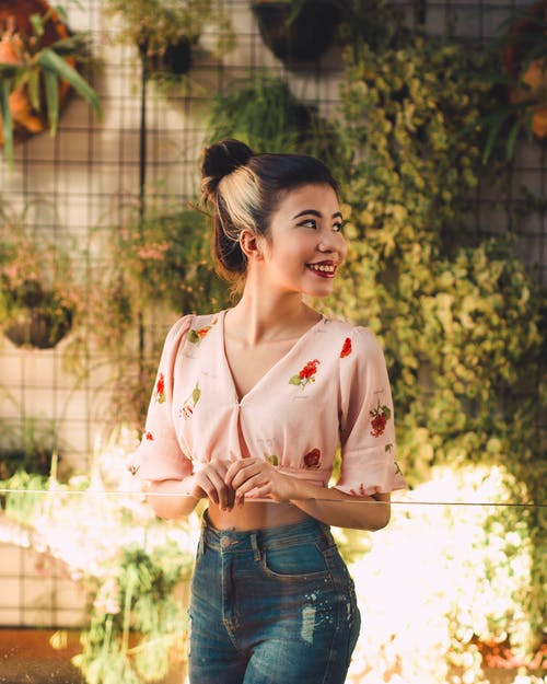 Woman in Pink Button Up Shirt and Blue Denim Shorts Standing Near Green Leaf Tree during