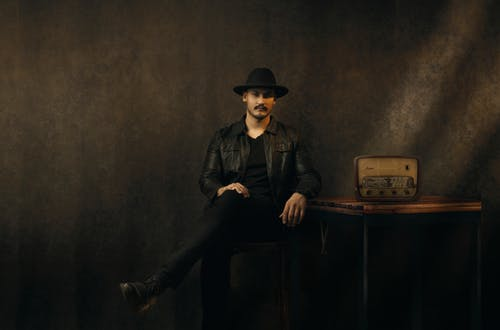 Man in Black Leather Jacket and Black Hat Sitting on Brown Wooden Table