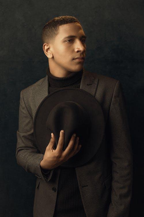 Boy in Black Suit Holding Black Hat