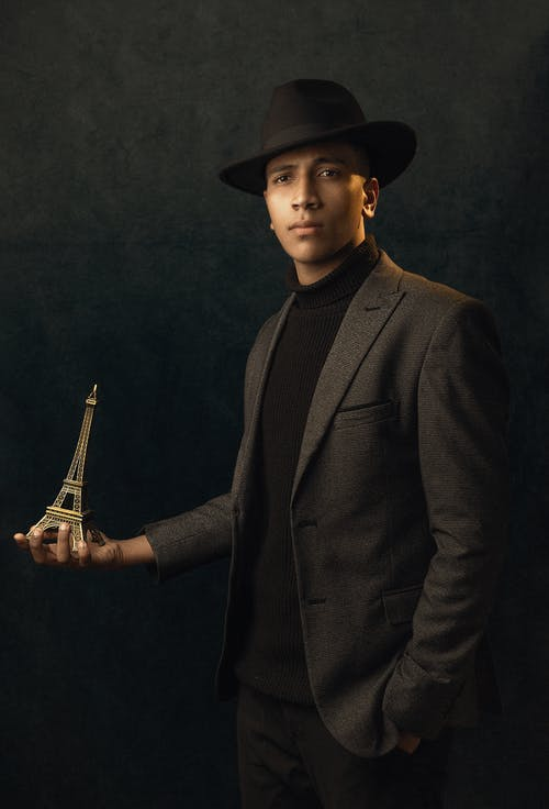 Man in Gray Suit Jacket and Black Hat Holding a Guitar