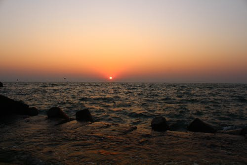Ingyenes stockfotó a tengernél, esti nap, homokkő, kék ég témában