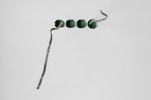 Green Beads with String on White Surface