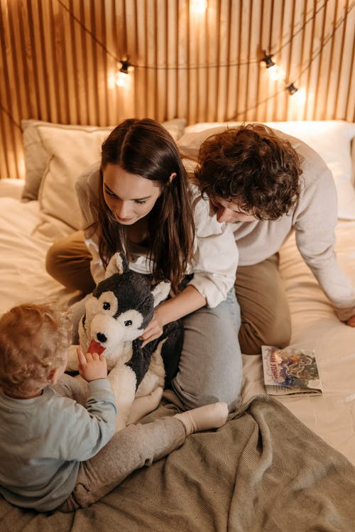 Mom Holding Dog Stuffed Toy In Front of Child