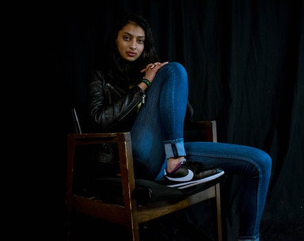 Woman Wearing Blue Jeans Sitting on Brown Wooden Armchair