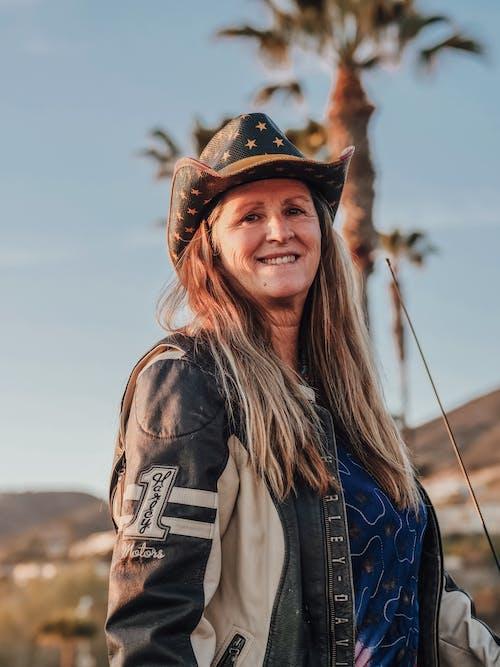 Woman in Brown Cowboy Hat and Brown Jacket