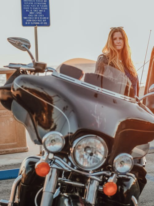 Woman in White Tank Top Riding on Brown and Black Motorcycle