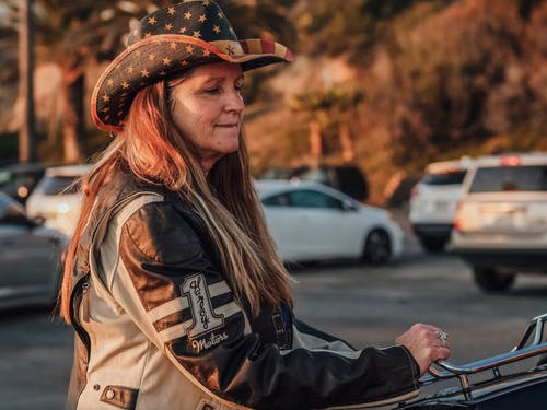 Woman in Black Leather Jacket and Brown Hat Standing on Road