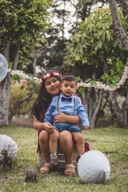Boy Sitting on Lap of Girl with Flower Headdress