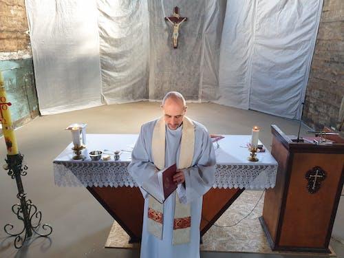 Man in White Thobe Standing Beside Table