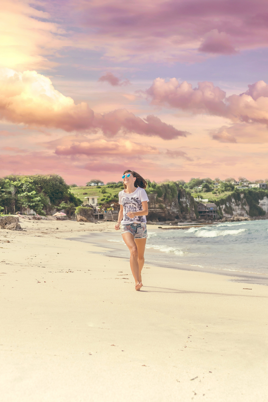 Smiling Woman Walking Barefood on Seashore Near Houses