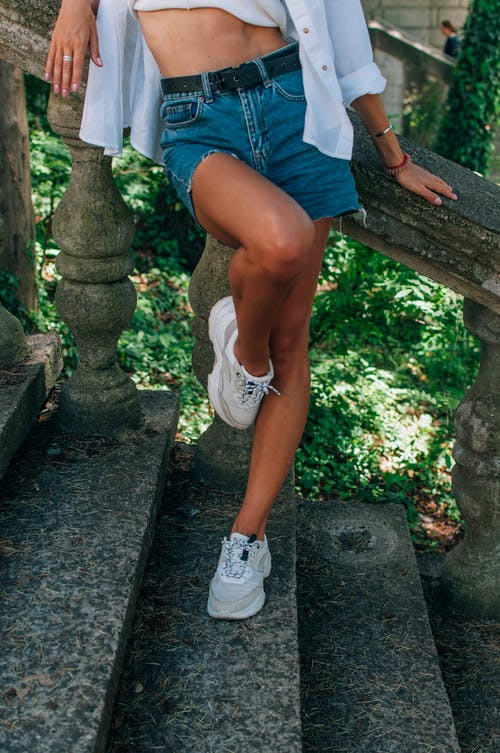 Woman in Blue Denim Shorts and White Sneakers Sitting on Brown Wooden Bench