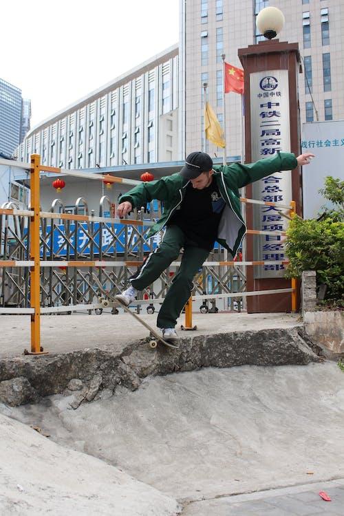 Man in Green Jacket Doing Skateboard Trick