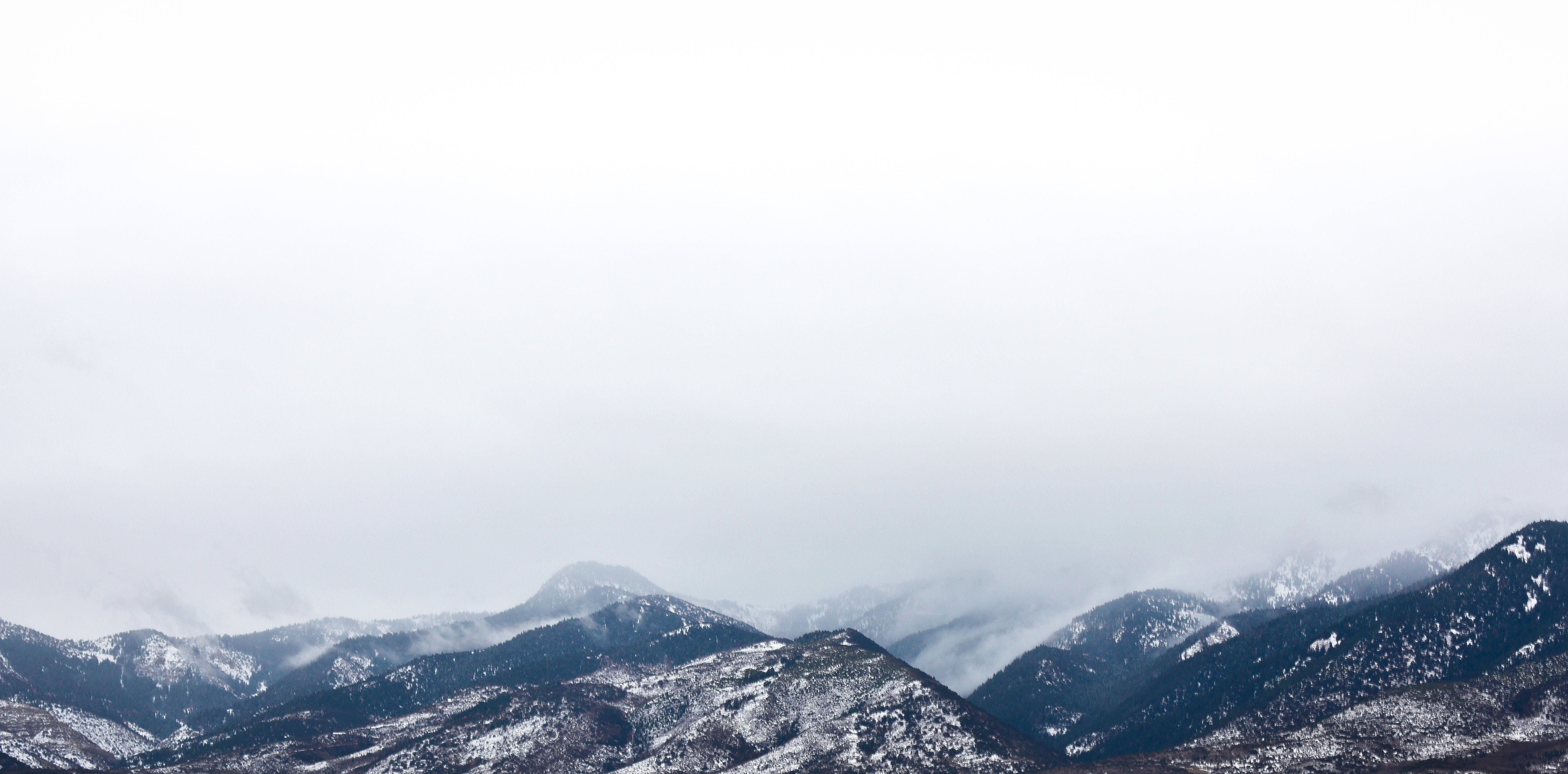 Snow Coated Mountain Under White Clouds