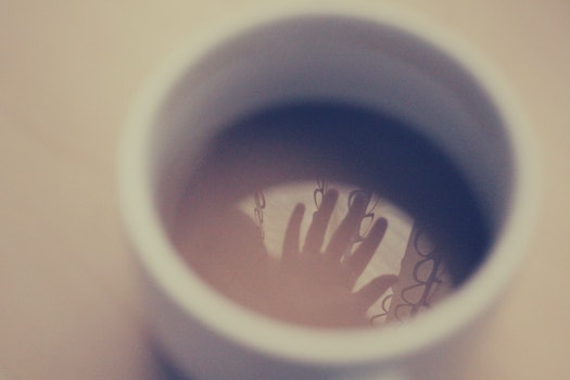 Silhouette of Hand in White Ceramic Cup