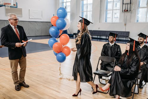 Photo of Graduating Student Approaching Teacher