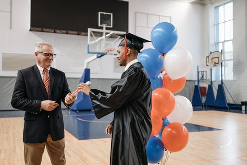 Photo of Man in Black Academic Gown Receives his Diploma
